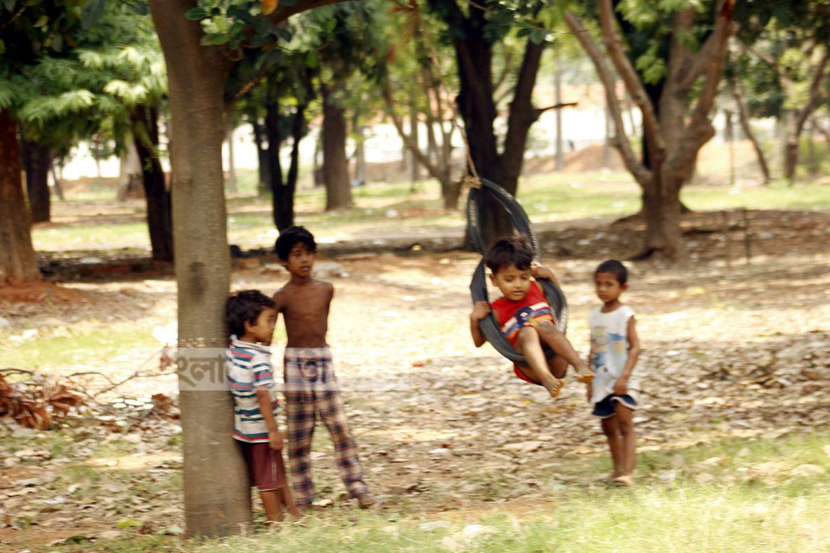রাজধানীর সোহরাওয়ার্দী উদ্যানে গাছে দোলনা বানিয়ে শিশুরা খেলছে। ছবি: ইলিয়াস সাজু