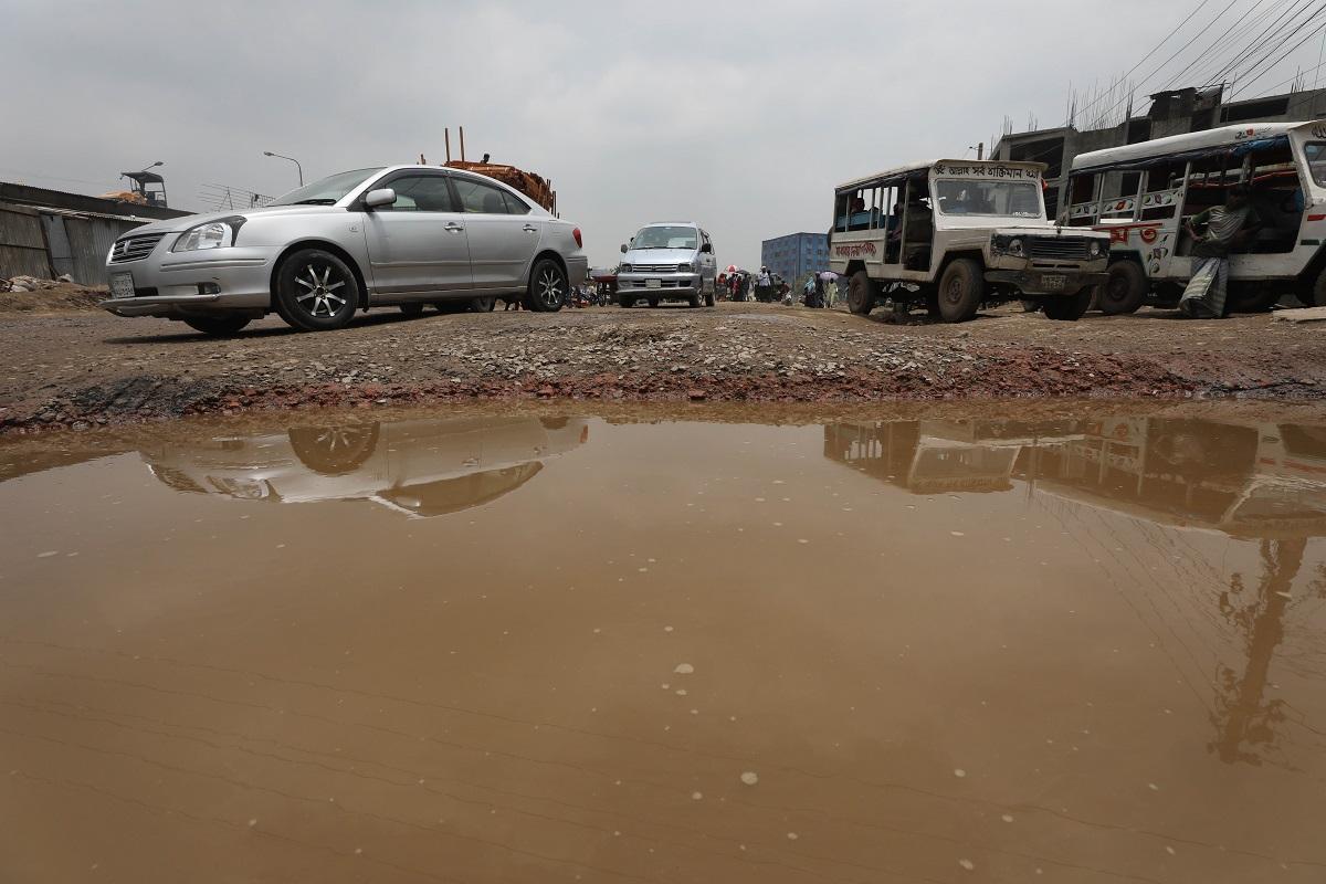 রাজধানীর পোস্তগোলা ব্রিজের নিচের রাস্তা খানাখন্দে ভরা।  জমে আছে পানিও, যানবাহন চলাচলে রাস্তা হয়ে যাচ্ছে সরু।  ছবিটি রোববার তোলা।